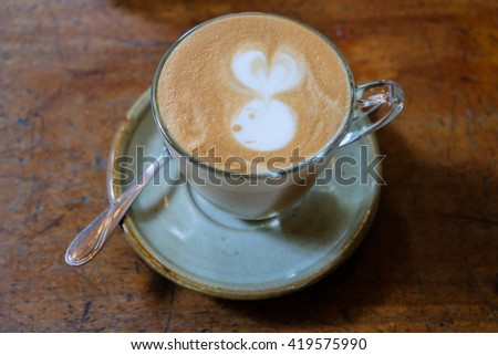 Coffee latte art on the wood desk at coffee shop. - stock photo