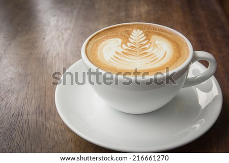 Coffee latte art on wood table - stock photo