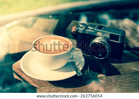 coffee latte art with classic camera  ;vintage tone style - stock photo