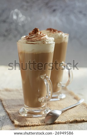 coffee latte macchiato with cream in glasses on window background, focus on the top, shallow DOF