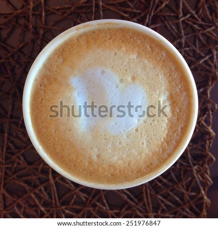 Coffee latte with steam milk on natural nest background