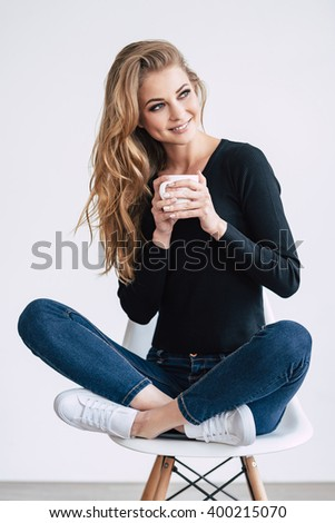 Coffee lover. Beautiful young woman holding coffee cup and looking away with smile while sitting on chair in lotus position against white background - stock photo