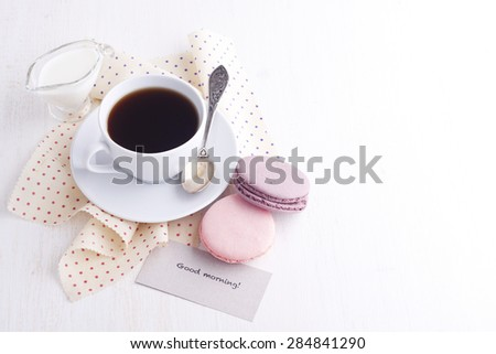 Coffee, macaroons and cream with a good morning card on a white table - stock photo
