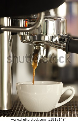 Coffee machine and white ceramic cup - stock photo