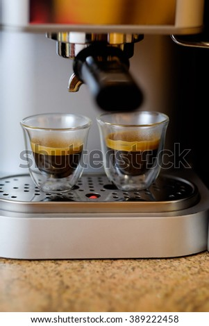 Coffee machine making, pouring fresh coffee into cups. Italian espresso coffee machine dispensing freshly brewed coffee into two small glass cups. Process of preparation of coffee, closeup. - stock photo