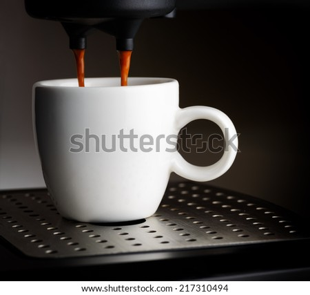 Coffee machine pouring a cup of espresso. - stock photo