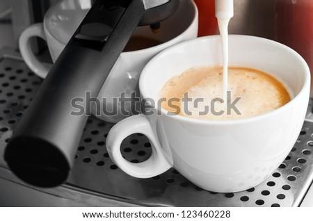 Coffee maker pouring hot milk in white cup to prepare cappuccino - stock photo