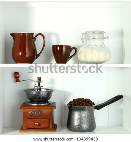 Coffee mill and coffee pot, cup and glass jar with sugar on white shelves - stock photo