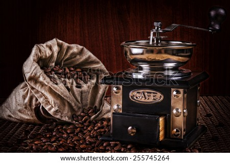 Coffee mill with burlap sack of roasted coffee beans. - stock photo