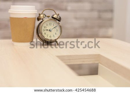 Coffee morning with Retro alarm clock on table on office background