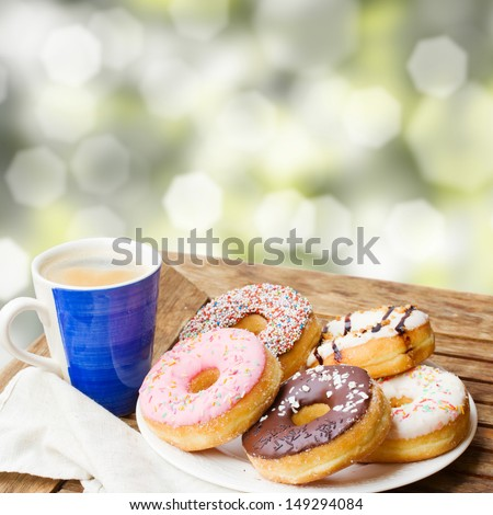 coffee mug and plate of donuts served on wooden table in garden - stock photo