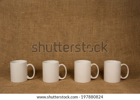 Coffee Mug Background.  Four white mugs in front of burlap.  Copy space on and above the mugs. - stock photo