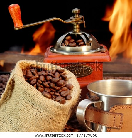 Coffee Mug, coffee beans   and grinder. Open fire in background. - stock photo