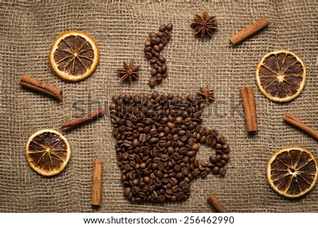 Coffee mug made from coffee beans with herbs and spices on burlab texture - stock photo