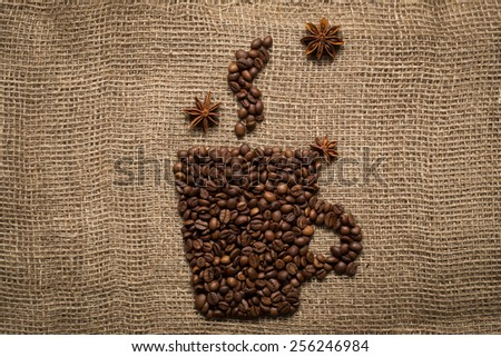 Coffee mug made from roasted beans with anise stars on burlap background - stock photo