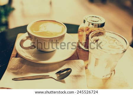 Coffee mug with brown sugar and glass of water set on wooden board with photo filter effect. - stock photo