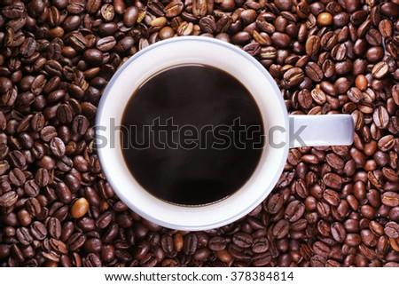 coffee mug with coffee on coffee bean texture - stock photo