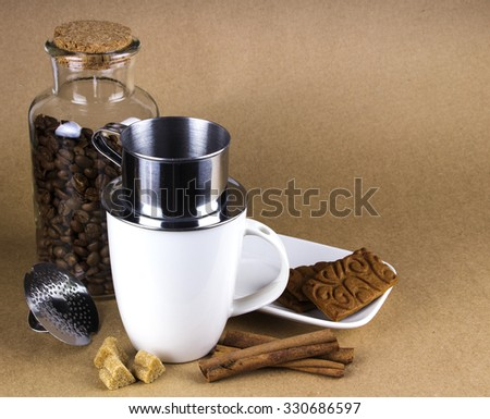 Coffee mug with dripper, and a glass jar of coffee beans.