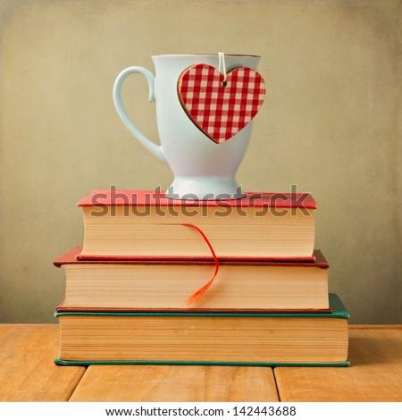 Coffee mug with heart shape on vintage books - stock photo