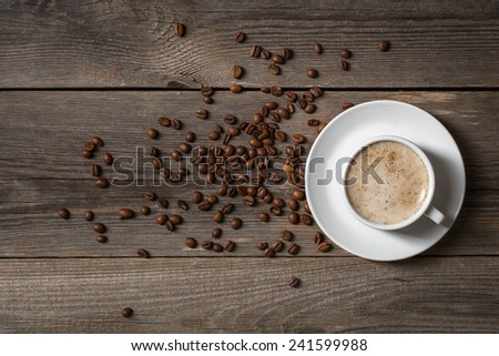 Coffee mug with roasted coffee beans on wooden table. View from top  - stock photo