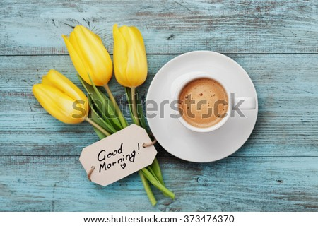 Coffee mug with yellow tulip flowers and notes good morning on blue rustic table from above, breakfast on Mothers day or Womens day - stock photo