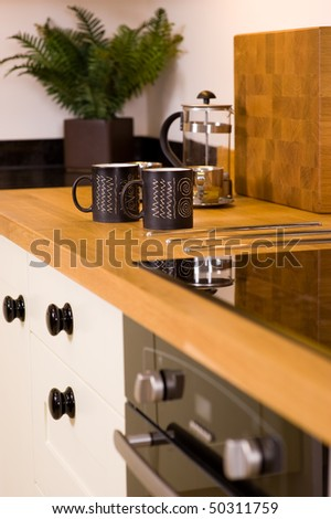 Coffee mugs and cafetiere on worktop in modern designer kitchen - stock photo