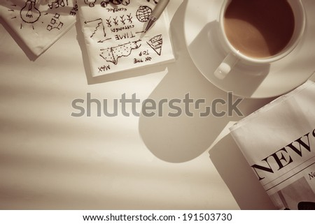 Coffee, newspaper and napkins with pictures, showing business breakfast - stock photo