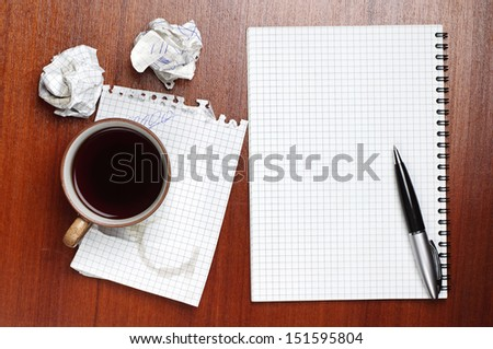 Coffee, notebook, pen and crumpled paper on table - stock photo