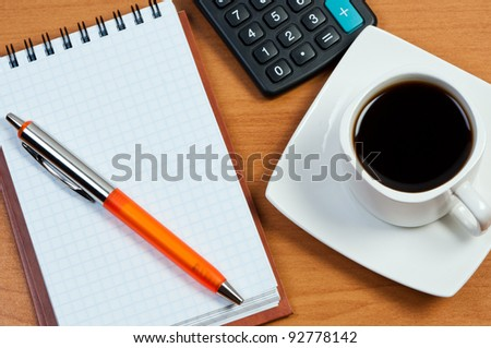 Coffee, notepad with pen and calculator on work-table.