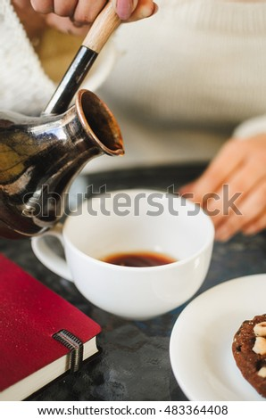 coffee on the table. on the table in the restaurant of hot coffee , a glass of water and biscuits. the girl pours coffee in a Cup