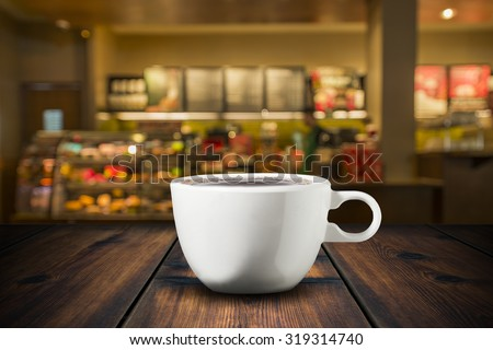 Coffee On Wood Table With Coffee Shop View In Background - stock photo