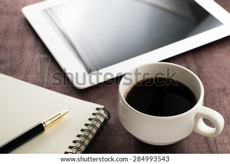 coffee pen book and tablet on wooden table