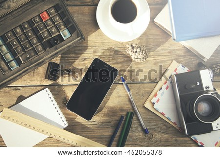 coffee, phone, camera, notebook and pen on table