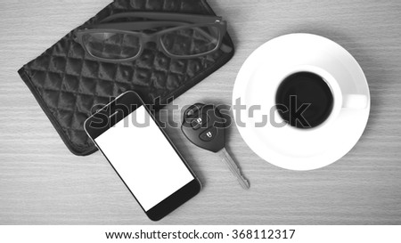 coffee,phone,car key,eyeglasses and wallet on wood table background black  and white color