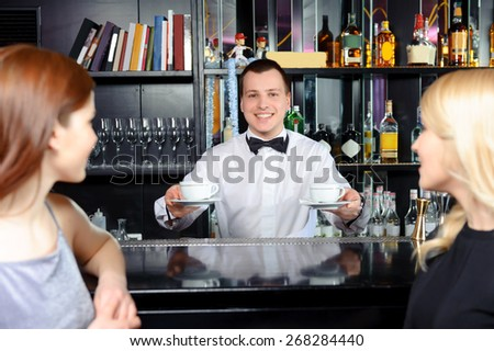 Coffee please. Young cheerful bartender stretching out two cups of coffee to female guests - stock photo