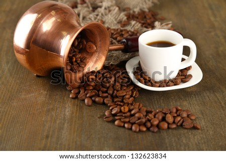 Coffee pot and cup on wooden background