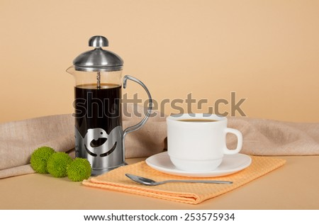 Coffee pot, cup with coffee, a teaspoon, a napkin on a sackcloth - stock photo