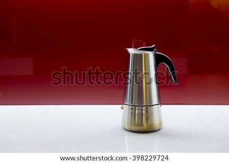 Coffee pot on table and red background - stock photo