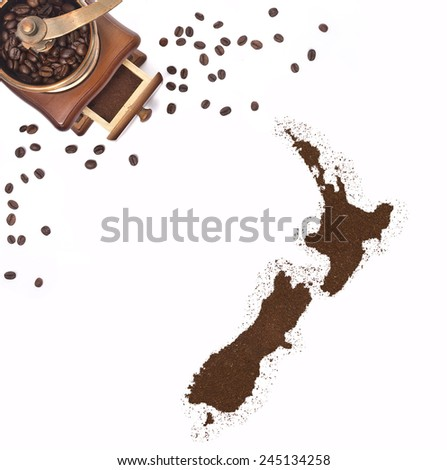 Coffee powder in the shape of New Zealand and a decorative coffee mill.(series) - stock photo