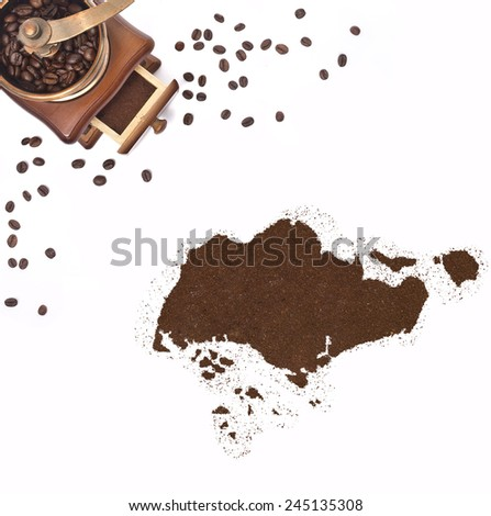 Coffee powder in the shape of Singapore and a decorative coffee mill.(series) - stock photo