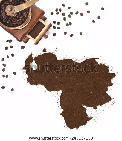 Coffee powder in the shape of Venezuela and a decorative coffee mill.(series) - stock photo