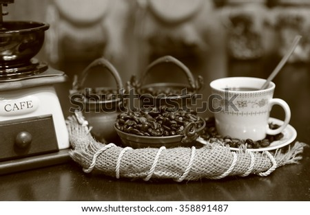 Coffee seeds and liquid in the cup with coffee grinder, black and white.
