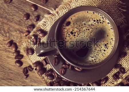 coffee served in a dark cup on wooden table on rustic style - stock photo