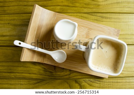Coffee set on a special support of a coffee cup, a spoon and a milkman. - stock photo