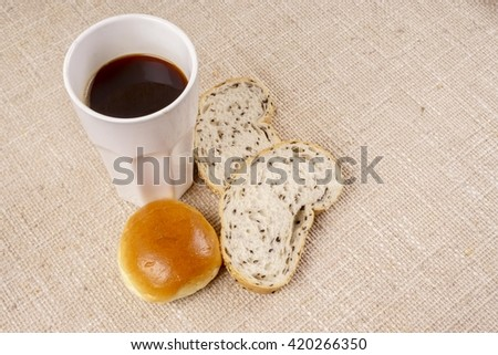 Coffee,slices of whole grain bread and bun for breakfast. Copy space