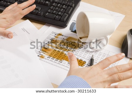 coffee spilled on important documents at a desk - stock photo