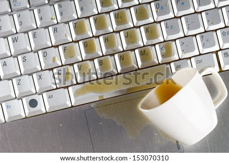 Coffee spilled on laptop keyboard - stock photo