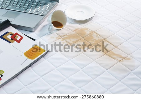 coffee spills on bed - stock photo