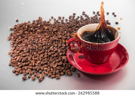 Coffee splash in red cup - stock photo