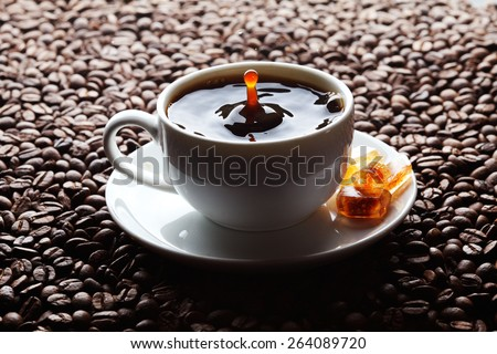Coffee splash in white cup over roasted coffee beans background - stock photo